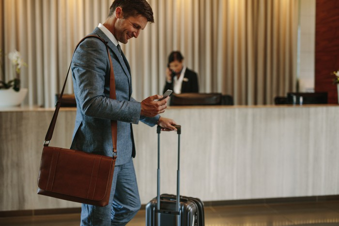 Man in suit checking phone in hotel lobby while holding wheeled suitcase and wearing shoulder bag
