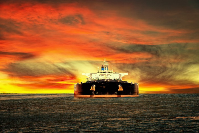 An oil tanker ship at sea with a sunset sky in the background.