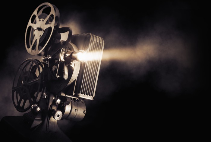 A film projector beams light out against a black background.