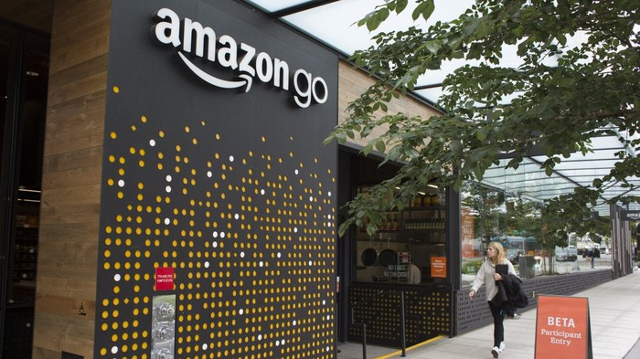 A woman walking down the sidewalk in front of an Amazon Go store.