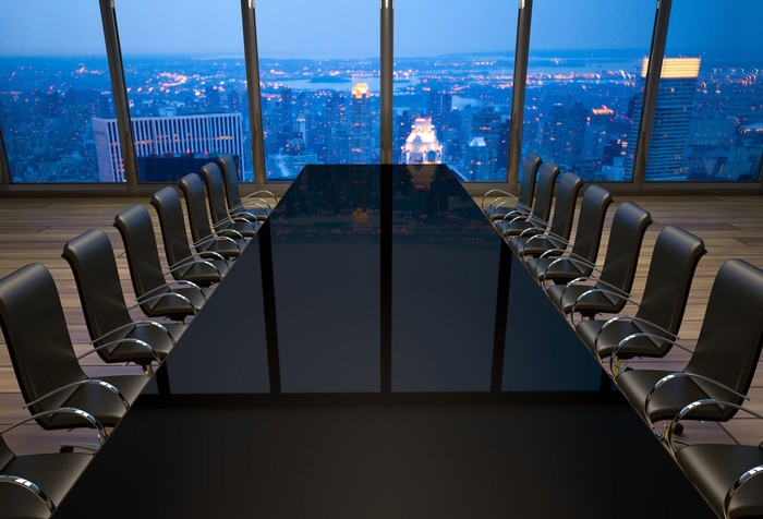 Empty boardroom table with a window overlooking a large city