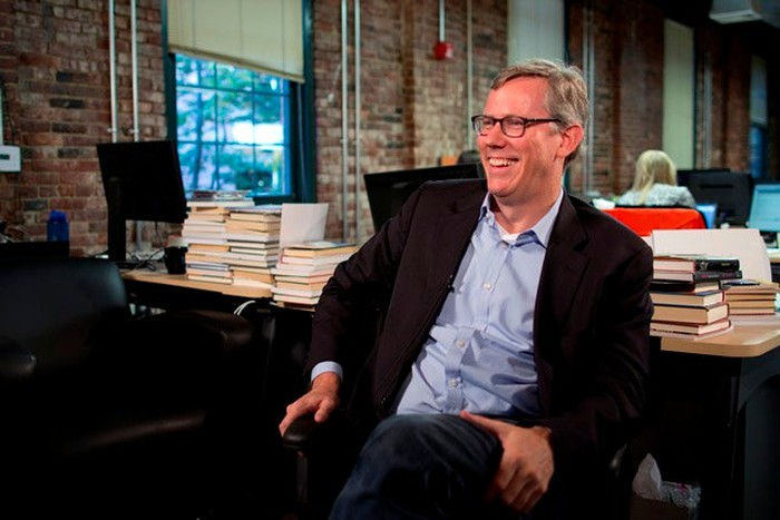 A photo of HubSpot CEO and co-founder Brian Halligan seated at a desk, turned around and facing left.