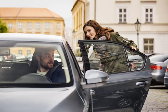 A woman getting into a black car with an Uber driver.