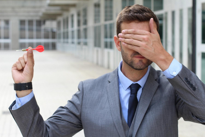 Man covering eyes throwing a dart.
