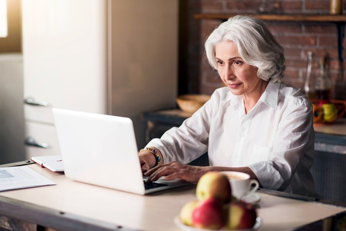 An older woman sits at a kitchen table, working on a laptop. A plate of apples is on the table.