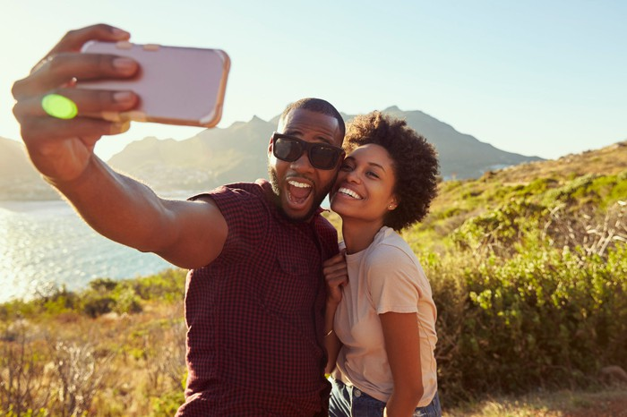 Smiling couple taking selfie in front of lake, with mountains in the background.