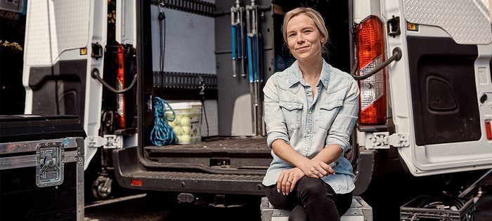 Woman sitting on truck tailgate holding Juul electronic cigarette