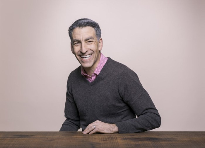 Profile photo of Redfin CEO Glenn Kelman sitting, left hand on a table.