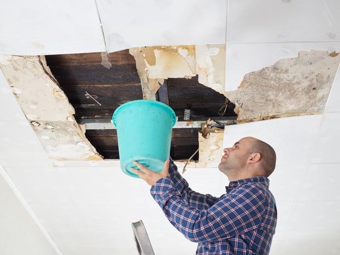 Man holding large bucket up to damaged ceiling
