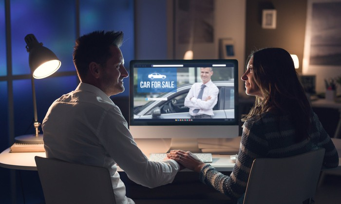 Man and woman looking at car buying options online.