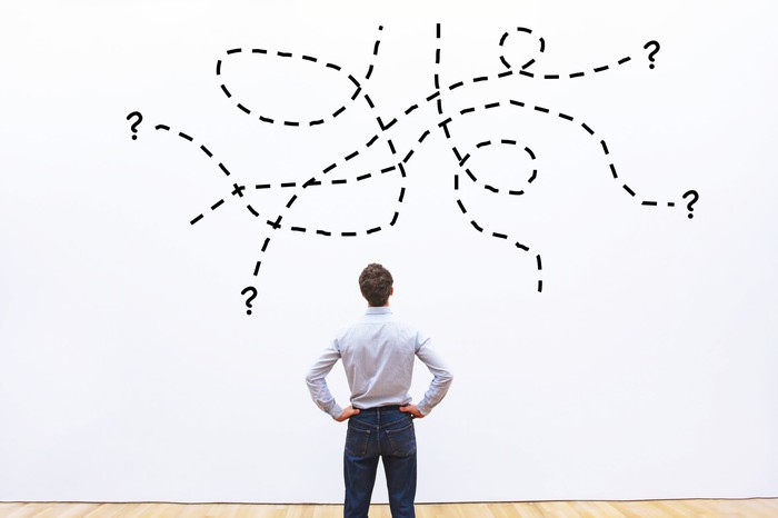 A man looks at a wall on which have been drawn question marks and dotted lines.