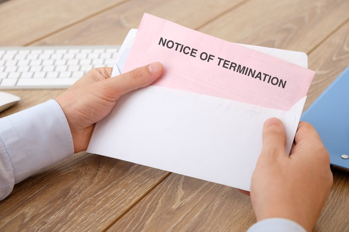 Man holding envelope with pink notice of termination sticking out