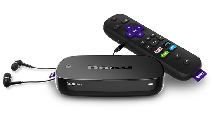 A shot of Roku's Ultra streaming video players with a remote and ear buds.