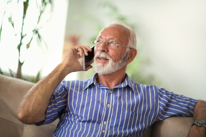 Seated senior man with beard in a blue shirt with white stripes, talking on mobile phone.
