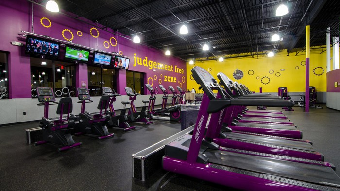 "An empty gym with treadmills and other equipment near a wall that shows the Planet Fitness motto, ""judgement free zone"""