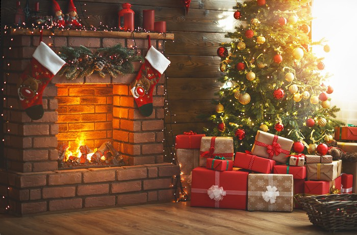 Presents under a Christmas tree by a fire