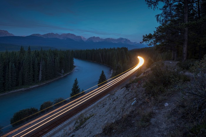 A locomotive's headlamps illuminate a river as rounds a bend by at night.
