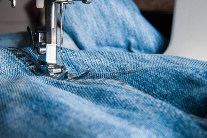 Jeans being manufactured using an industrial stitcher.