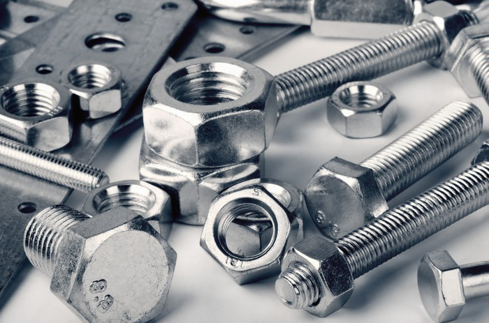 Close up of shiny industrial fasteners and assorted nuts and bolts.