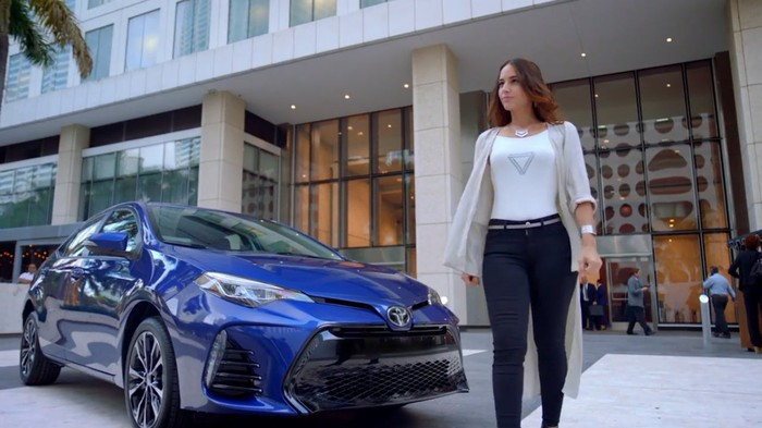 A model walking in front of a showroom vehicle.