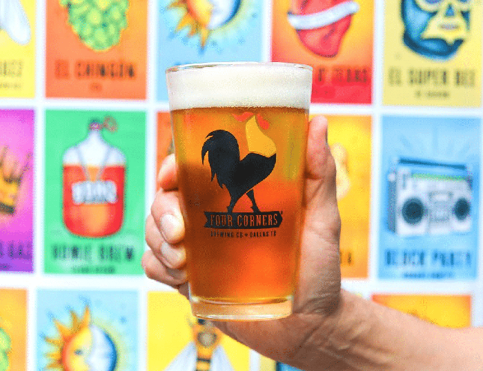 Hand holding glass of four corners beer