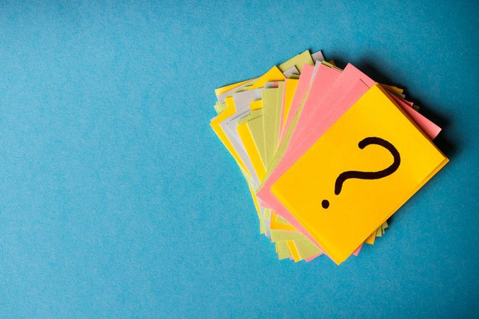 A pile of colorful cards on a blue background, with the topmost card having a question mark drawn on it