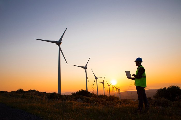 A person with a laptop inspecting wind turbines.