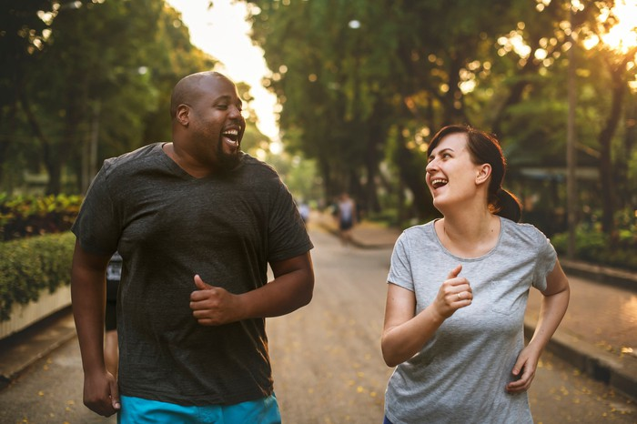 Two people out for a run smiling at each other.