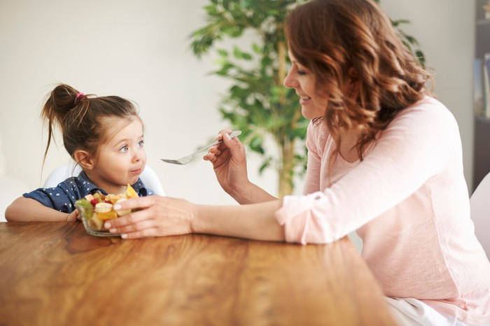 Woman sitting across from young girl at table and holding fork near her mouth