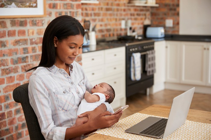 Woman at laptop sitting in a kitchen and checking phone while holding baby.