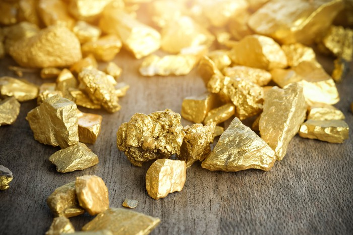 Shimmering gold nuggets on a wooden table.