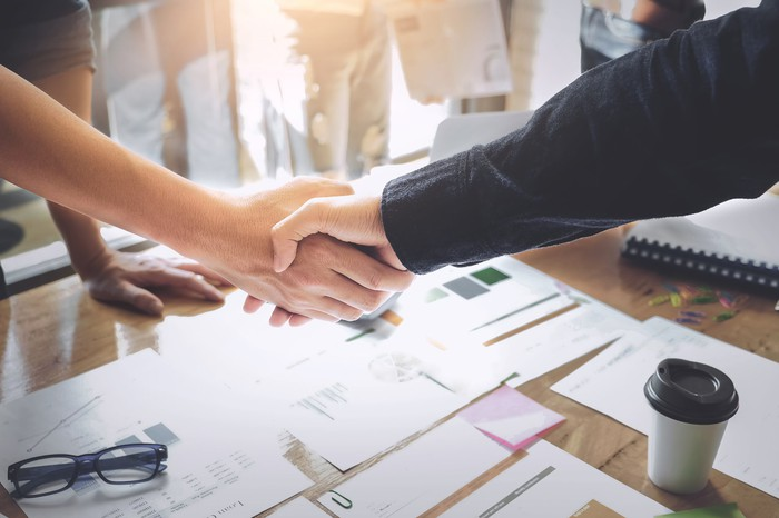 Two businesspeople shake hands over a conference table.