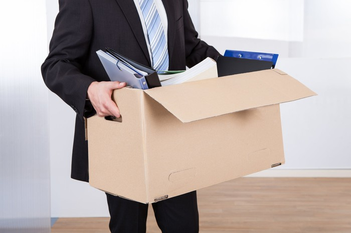 Man in suit carrying cardboard box with laptop and papers sticking out