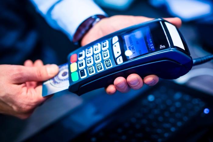 A merchant uses a credit card reader.