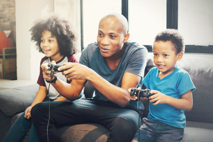 A father plays a video game with his two children.
