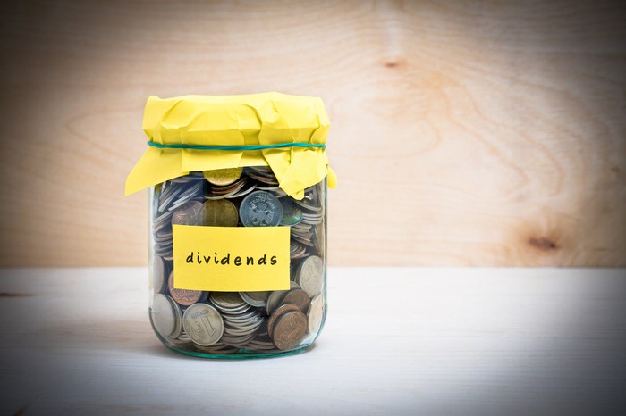"A jar with a yellow cover marked ""dividends"" and filled with coins sits on a table."