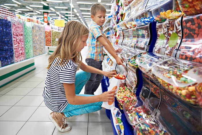 A girl and a boy filling candy into a bag in a store aisle.