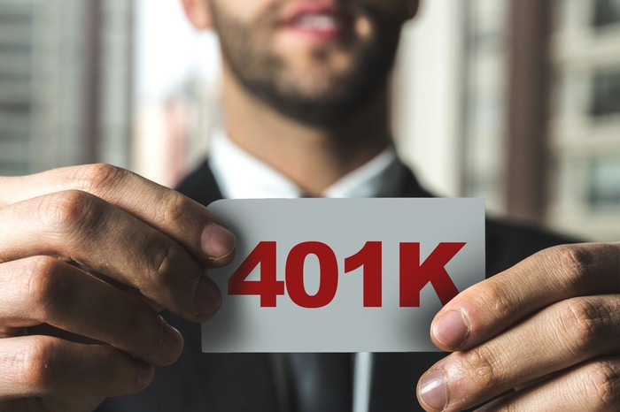 Man in suit holding up a small white piece of paper reading 401K in red letters