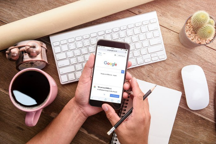 Overhead view of a person's hands holding a cell phone with Google's home page showing. Various desk-top items, such as a keyboard, shown.