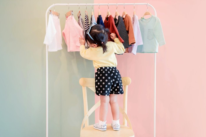 A female toddler browses through a rack of clothes.