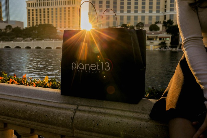 A Planet 13 bag on railing next to a seated person.