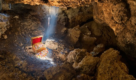Cave with skylight streaming sunlight on a treasure chest.