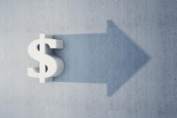 A dollar sign on a wall casting a shadow that's an arrow.