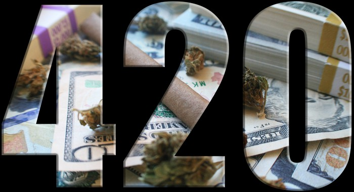 420 with U.S. cash and cannabis buds displaying through the numbers