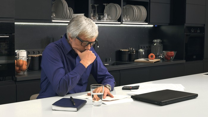 Gray-haired man at table looking at documents; near him are a water glass, notebook with pen resting on it, and closed laptop