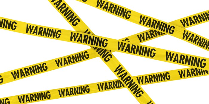 Yellow police tape is criss-crossed across the image, with the word warning printed repeatedly on it.