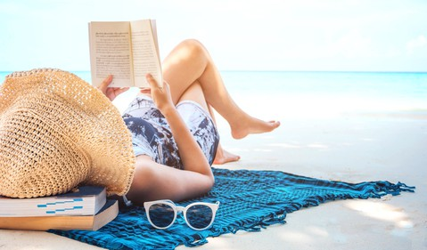 woman reading on beach_GettyImages-942466852