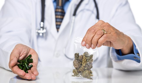 doctor-holding-marijuana-and-capsules-getty