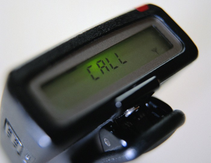 "A pager with a message that says ""Call."""
