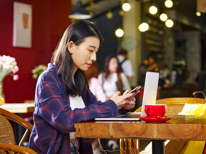 A young woman checks her phone and laptop in a coffee shop.